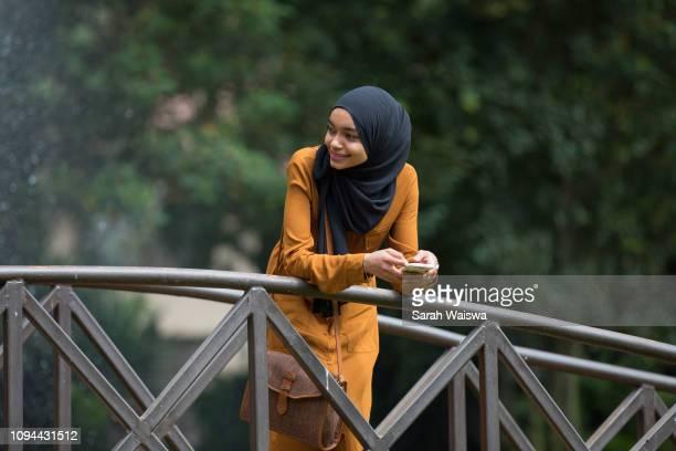portrait of a woman in a hijab on a bridge - zurückhaltende kleidung stock-fotos und bilder