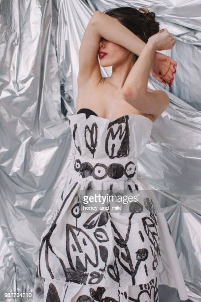 portrait of a woman in a paper dress with her arms covering her face - strapless evening gown stock pictures, royalty-free photos & images
