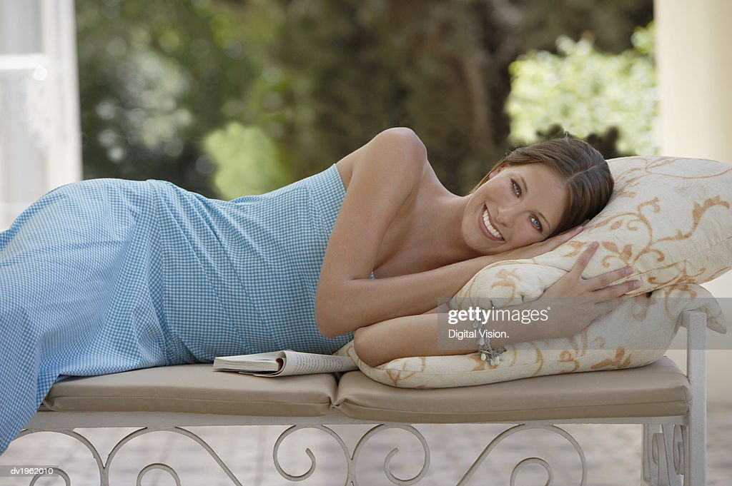 Portrait of a Woman in a Strapless Dress Lying on a Bench : Stock Photo