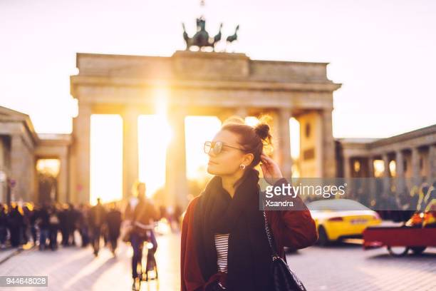 portrait of a woman in front of brandenburger tor in berlin, germany - city break stock pictures, royalty-free photos & images