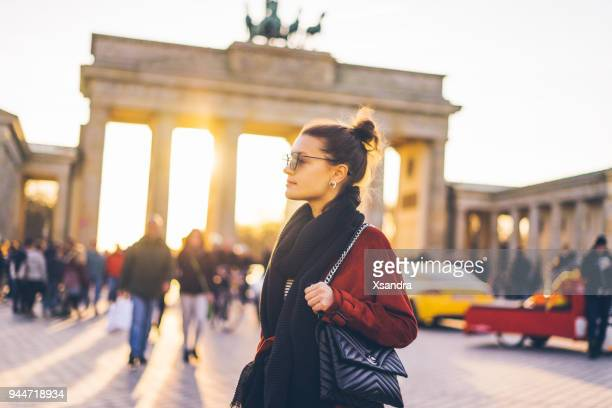 portrait of a woman in front of brandenburger tor in berlin, germany - central berlin stock pictures, royalty-free photos & images