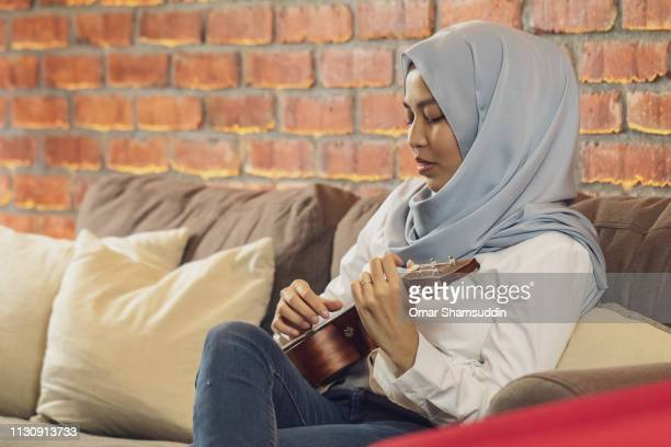 Portrait of a woman in hijab playing ukulele