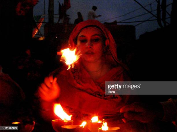 Portrait of a woman in pilgrimage lighting candles inside the shrine of Lal shahbaz Qalandar a 13th century Sufi Master worshiped alike by Hindus and...