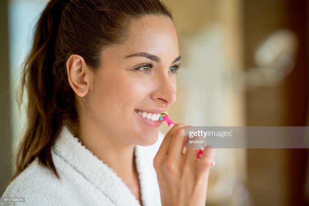 Portret van een vrouw in de badkamer haar tanden poetsen : Stockfoto