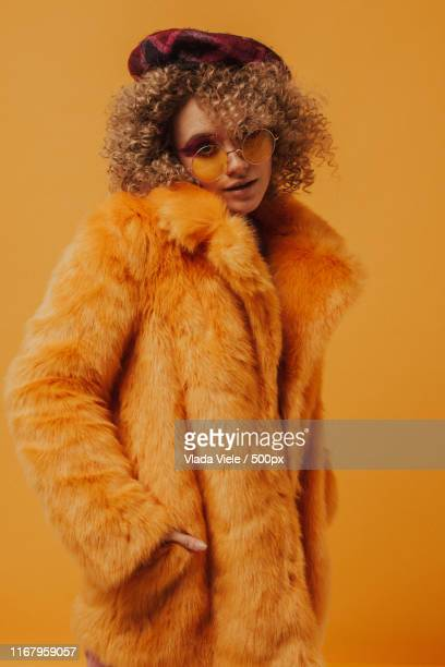 portrait of a woman in yellow tones - fur coat stock pictures, royalty-free photos & images