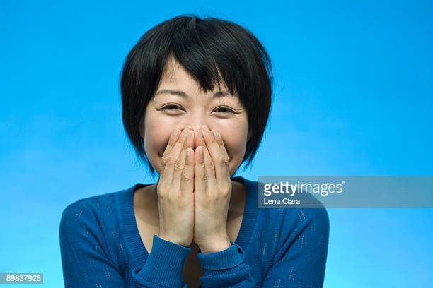 Portrait of a woman laughing and covering her face