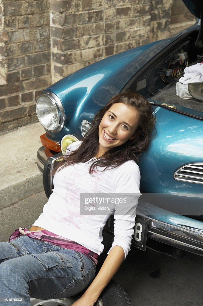 Portrait of a Woman Leaning Against a Classic Car with it's Bonnet open : Stock Photo