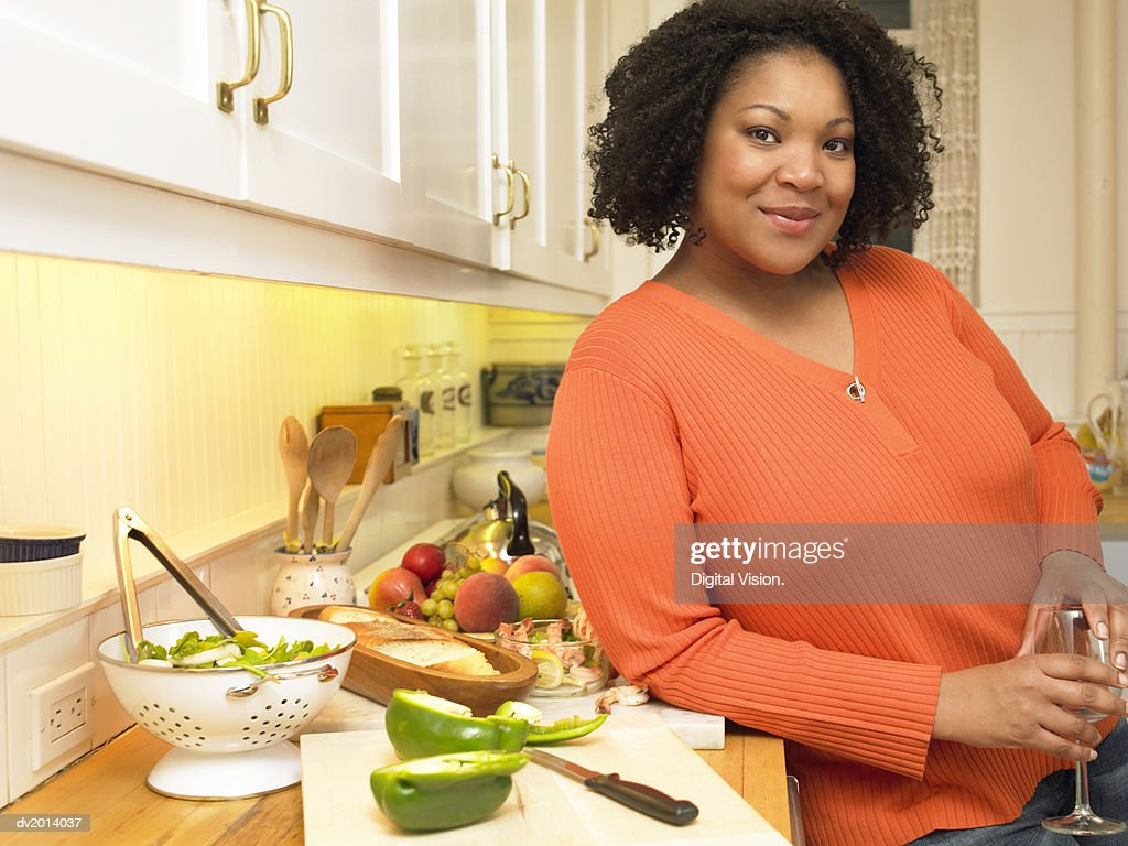 Portrait of a Woman Leaning on a Kitchen Counter, Preparing a Salad With Green Pepper : ストックフォト