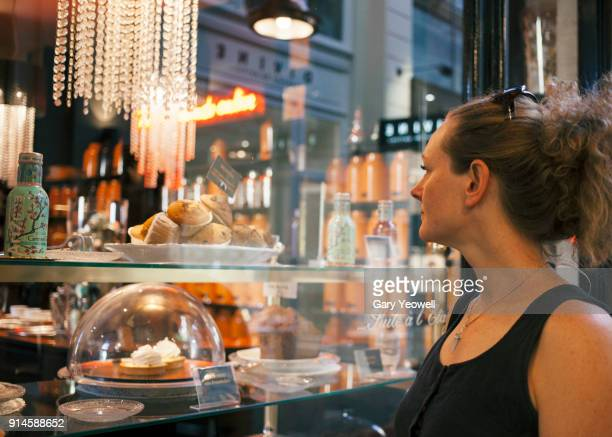 Portrait of a woman looking into a cake shop window