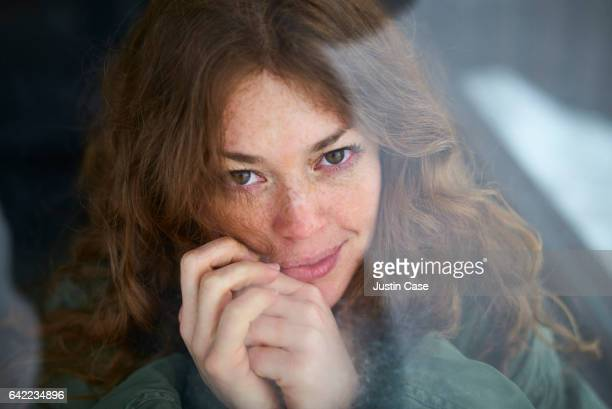 Portrait of a woman looking out of a window