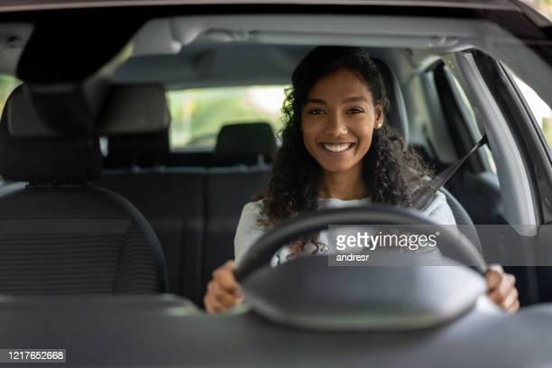 ritratto di una donna che sembra molto felice alla guida di un'auto - guidare foto e immagini stock