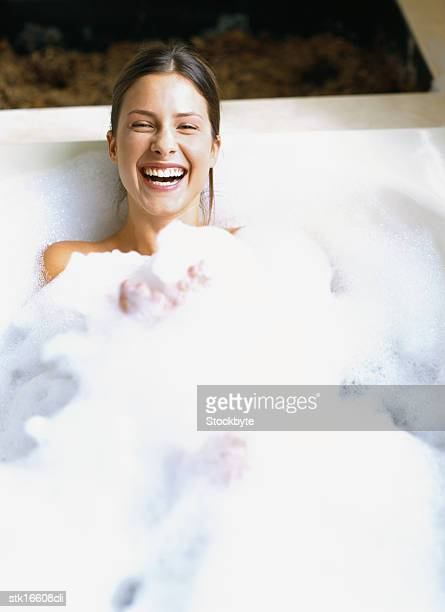 portrait of a woman lying in a bubble bath - bubble bath stock pictures, royalty-free photos & images
