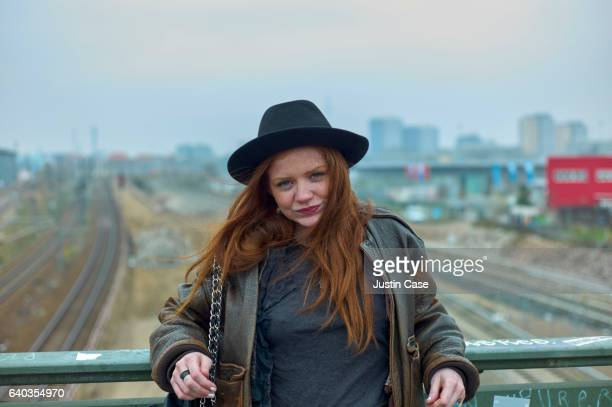 portrait of a woman on a bridge above railway tracks