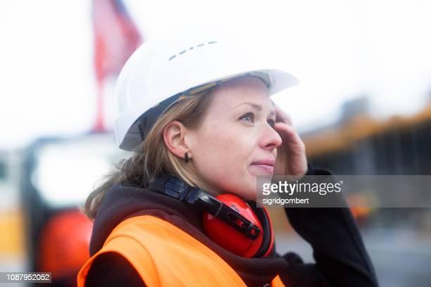 portrait of a woman on a construction site - une seule femme d'âge moyen photos et images de collection