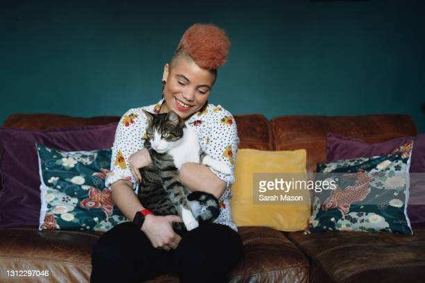 portrait of a woman on sofa with cat - one mid adult woman only stock pictures, royalty-free photos & images