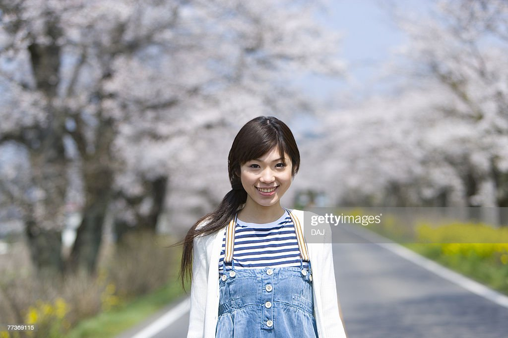 Portrait of a woman on the road lined with cherry trees, smiling and looking at camera, front view, Japan : Photo