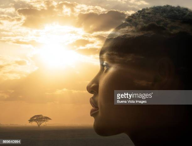 Portrait of a woman over an african landscape