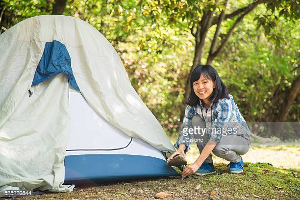 Portrait of a woman pitching a tent