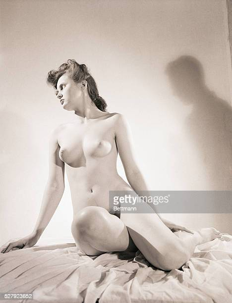 Portrait of a woman posing nude A man's shadow appears on the wall behind her Undated photograph circa 1950's