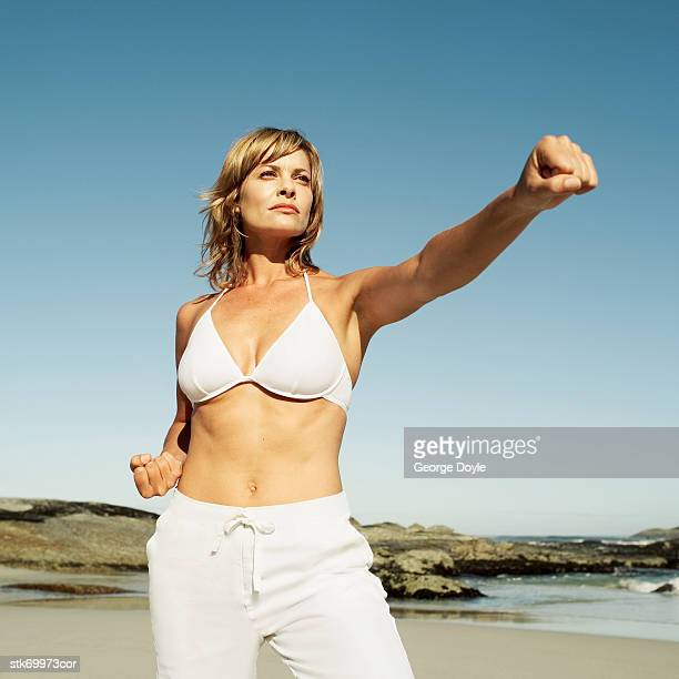 portrait of a woman practicing martial arts on the beach