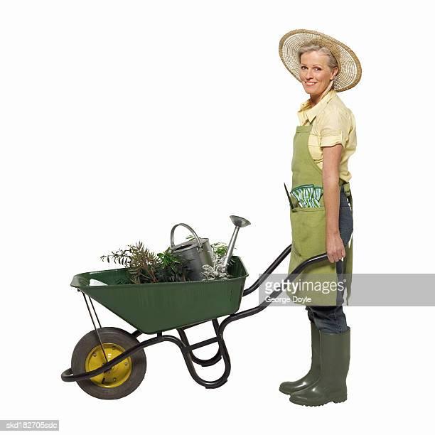 portrait of a woman pushing a wheelbarrow