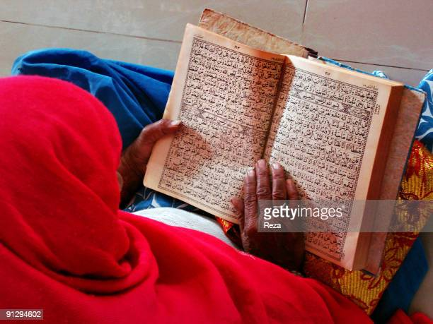 Portrait of a woman reading the Quran inside the shrine of Bodla Bahhar, one of the main disciples of Lal Shahbaz Qalandar, a 13th century Sufi...