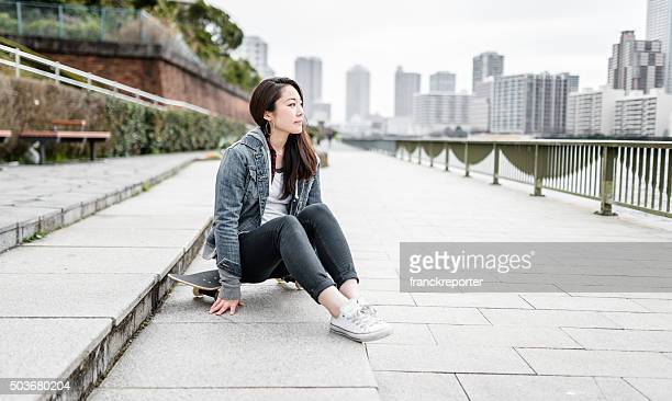 portrait of a woman relaxing with her skateboard