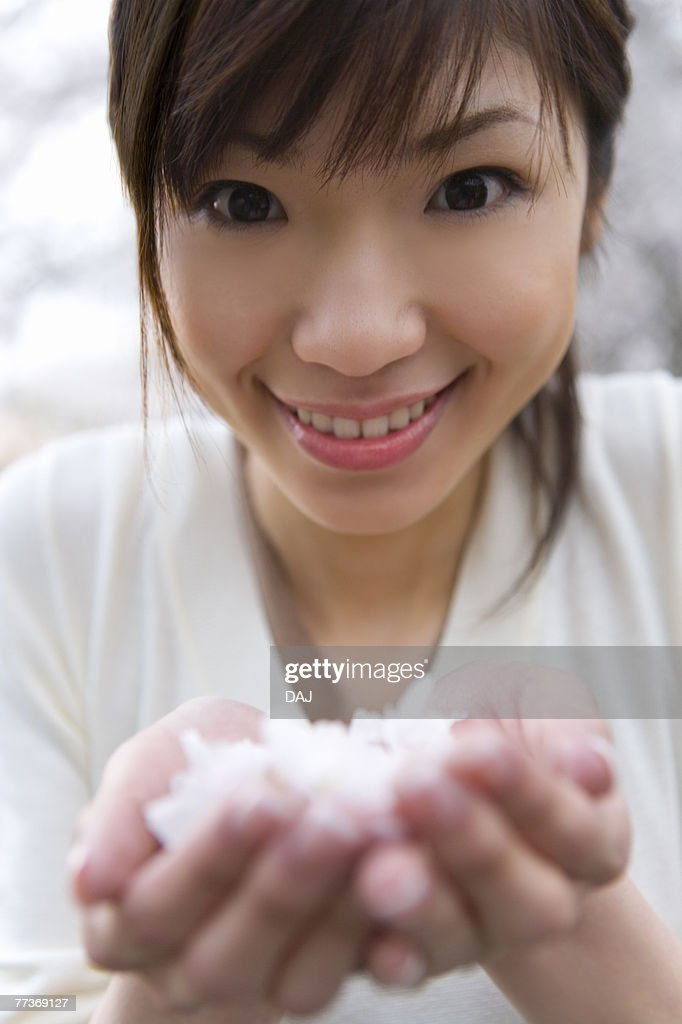 Portrait of a woman scooping up cherry flowers with hands, smiling and looking at camera, front view, close up, Japan : Photo
