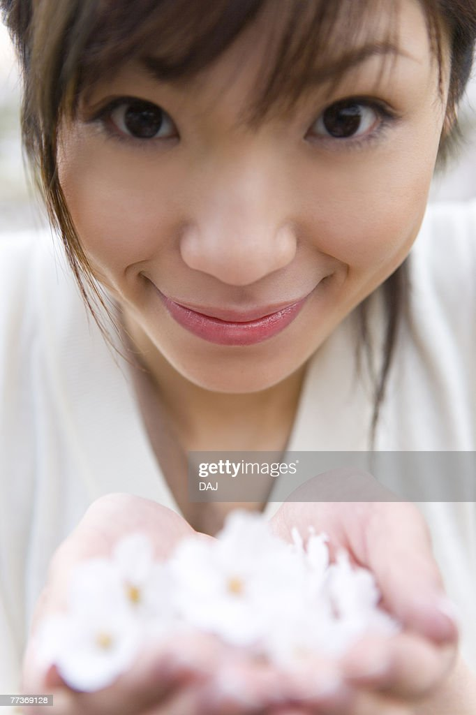 Portrait of a woman scooping up cherry flowers with hands, smiling and looking at camera, front view, close up, differential focus, Japan : Photo