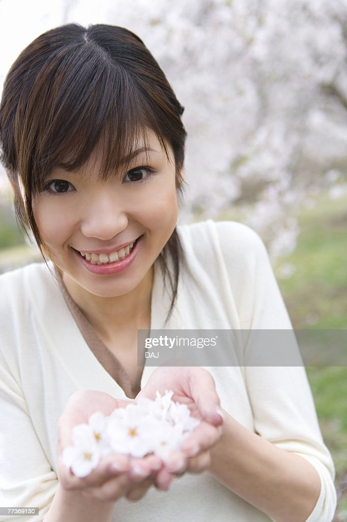 Portrait of a woman scooping up cherry flowers with hands, smiling and looking at camera, front view, Japan : Photo