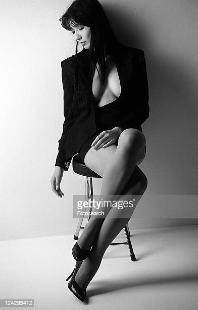 Portrait of a woman sitting and looking down, legs crossed at knee, black and white, front view, white background