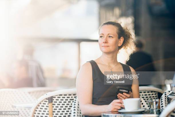 portrait of a woman sitting at a cafe table in bordeaux - one mature woman only stock pictures, royalty-free photos & images