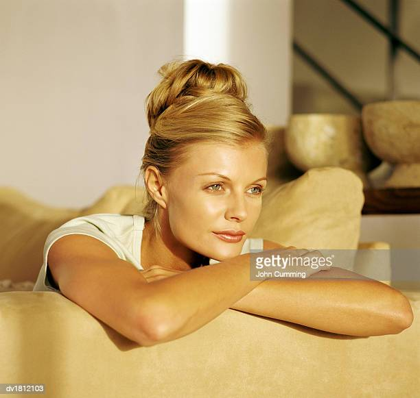 Portrait of a Woman Sitting on a Suede Sofa, Gazing Ahead Contemplatively