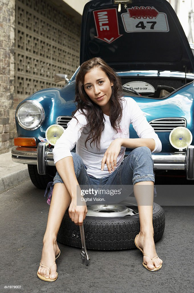 Portrait of a Woman Sitting on a Tyre and Holding a Ratchet, with a Car with it's Bonnet Open in the Background : Stock Photo