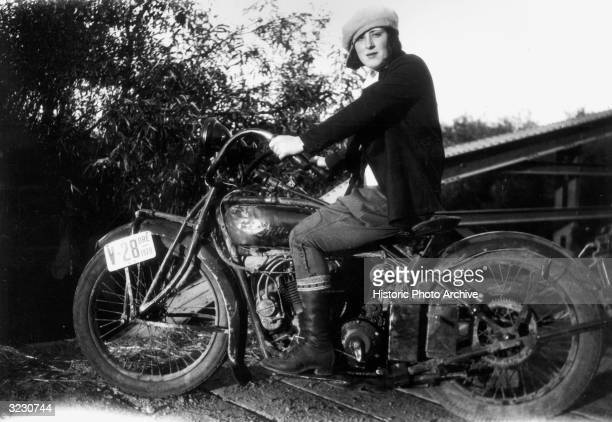 Portrait of a woman sitting on an Indian motorcycle on top of a wood planked bridge, Oregon. She wears a cap turned to one side.