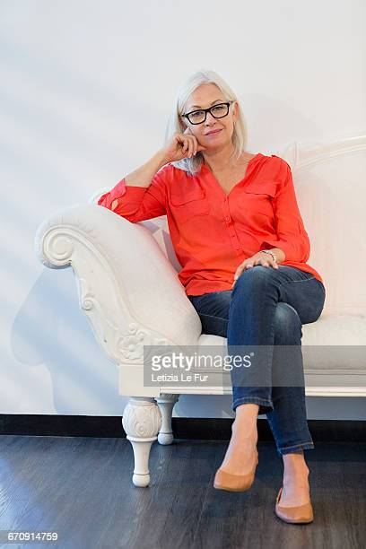 portrait of a woman sitting on sofa - smart casual stock pictures, royalty-free photos & images
