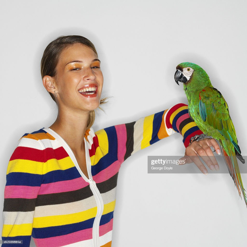 portrait of a woman sitting with a parrot on her arm : Stock Photo