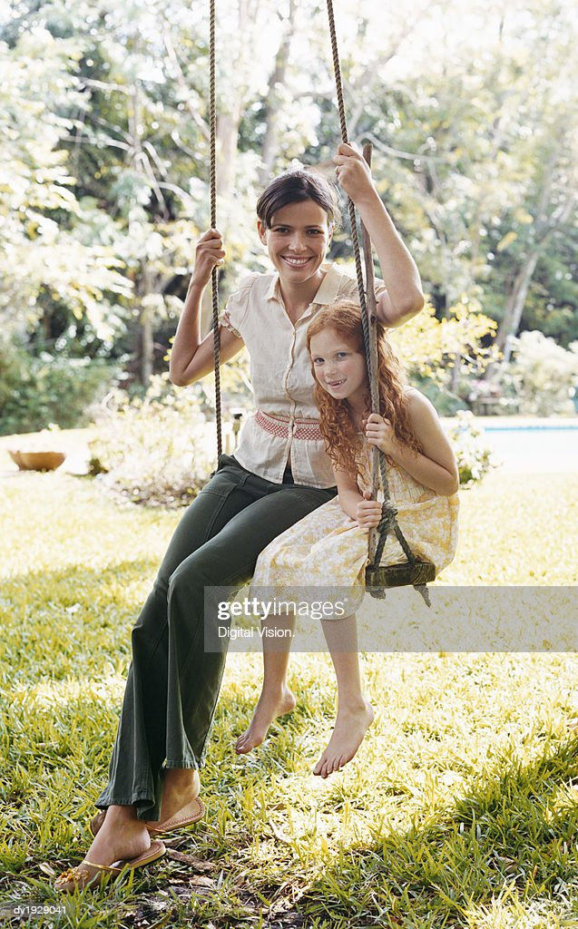 Portrait of a Woman Sitting With Her Young Daughter on a Swing in a Garden : Stock Photo