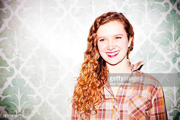 Portrait of a woman smiling against a wall