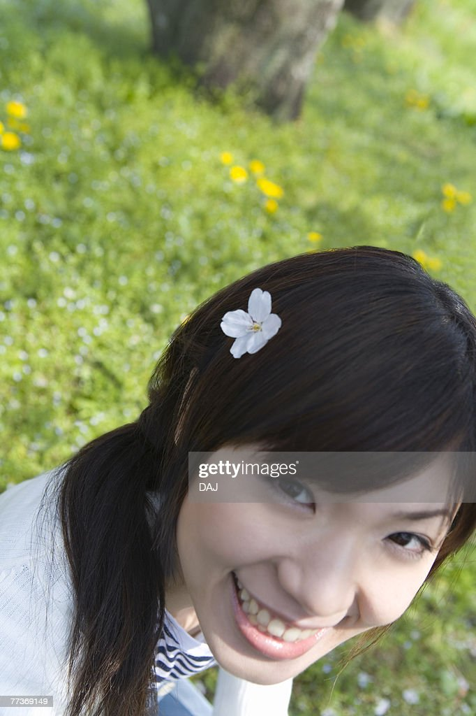Portrait of a woman smiling and looking at camera, cherry flower on her hair, high angle view, Japan : Stock Photo