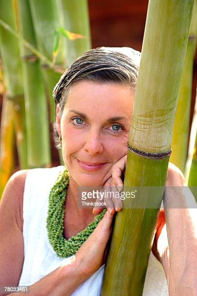 Portrait of a woman smiling at the viewer and leaning on a bamboo tree.