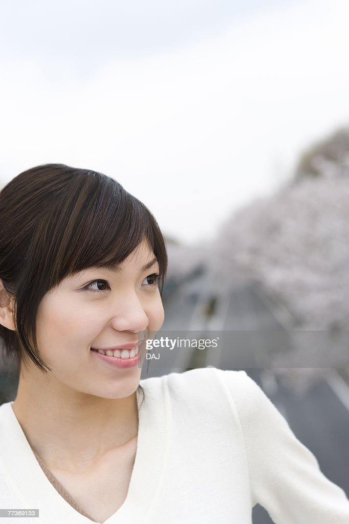Portrait of a woman smiling, road lined with cherry trees in the background, front view, Japan : Photo