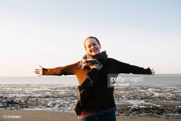 portrait of a woman smiling with open arms by the sea - scarf stock pictures, royalty-free photos & images