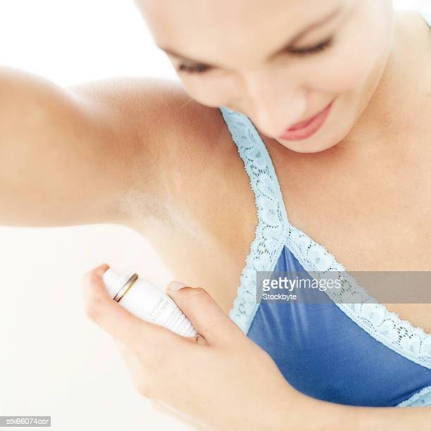 portrait of a woman spraying deodorant under her arm