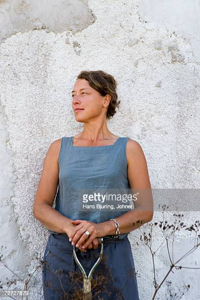 Portrait of a woman standing by a house wall.