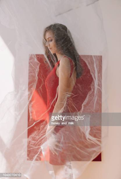 Portrait of a woman standing by a red wall behind a veil