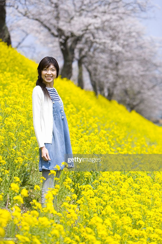 Portrait of a woman standing in rape field, smiling and looking at camera, side view, Japan : Photo