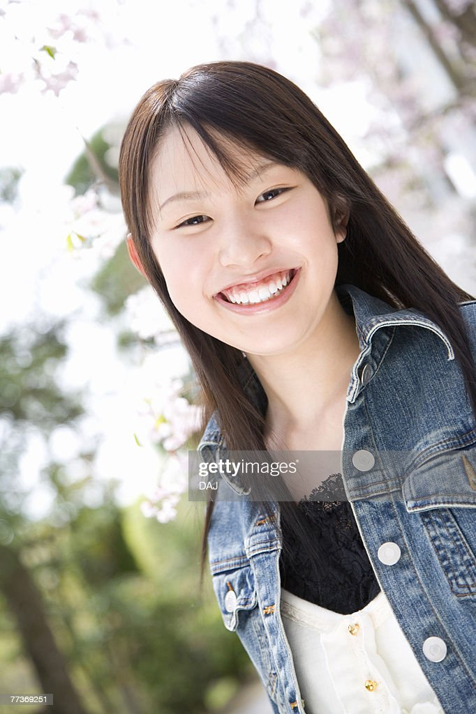 Portrait of a woman standing under the cherry tree, smiling and looking at camera, front view, Japan : Photo