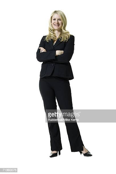 portrait of a woman standing with her arms crossed - pant suit stock pictures, royalty-free photos & images