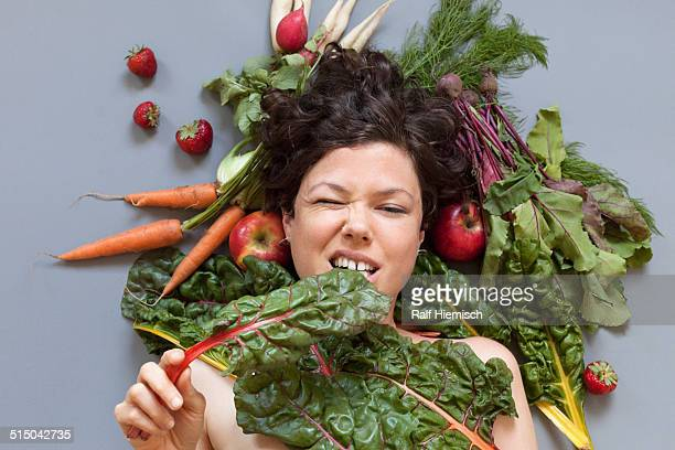 Portrait of a woman surrounded by vegetables biting rhubarb leaf over grey background